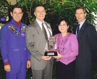 Intek owners Joseph and Marilyn Harpster accept award from astronaut Bob Cabana and Boeing's ISS Vice President and General Manager Brewster Shaw.